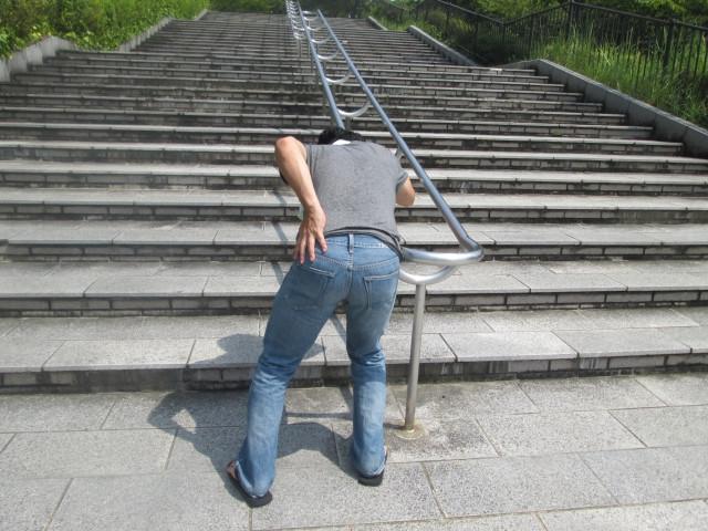 腰の痛みで階段が登れない男性の写真
